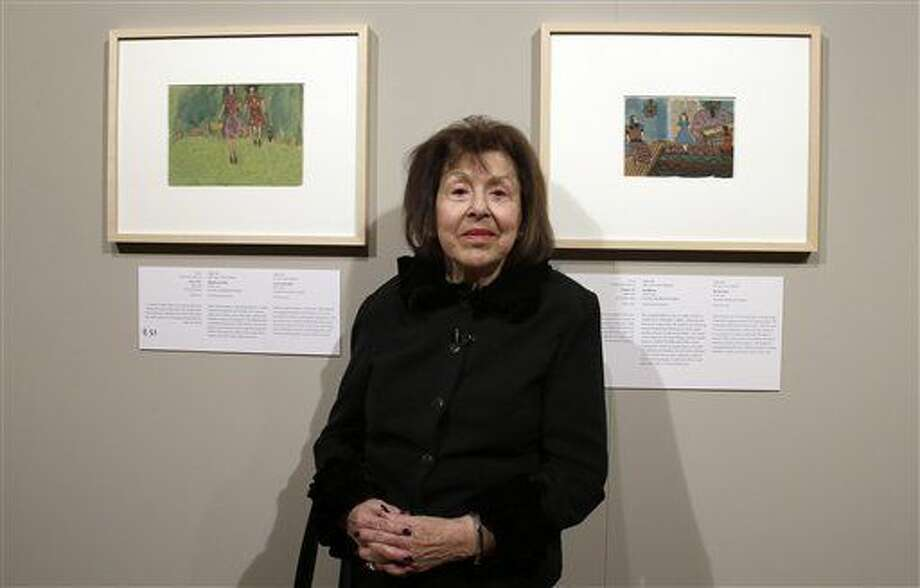 Artist Nelly Toll poses between two of her paintings during the exhibition 'Art from the Holocaust - 100 Works from the Yad Vashem Collection' at the German Historic Museum in Berlin, Germany, Monday, Jan. 25, 2016. (AP Photo/Michael Sohn)