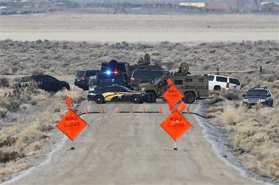 Law enforcement personnel block an access road to the Malheur National Wildlife Refuge, Wednesday, Jan. 27, 2016, near Burns, Ore. Authorities were restricting access on Wednesday to the Oregon refuge being occupied by an armed group after one of the occupiers was killed during a traffic stop and eight more, including the group's leader Ammon Bundy, were arrested. (Thomas Boyd/The Oregonian via AP)