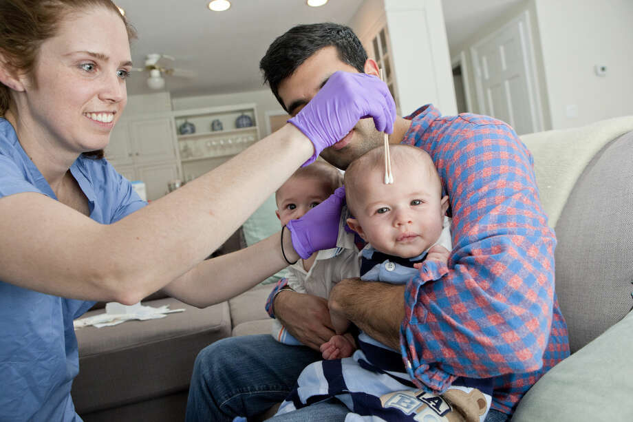 This image provided by John Abbott via New York University shows NYU senior research coordinator Nora Henderson collecting samples of bacteria from twin boys at their Mamaroneck, N.Y., home on Friday, Jan. 29, 2016. We share our bodies with microbes that help keep us healthy, and the babies are part of research at NYU Langone Medical Center that gives infants born by C-section a dose of bacteria from mom's birth canal to see if it influences development of their own so-called microbiome. (John Abbott/NYU Langone Medical Center via AP) Photo: John Abbott