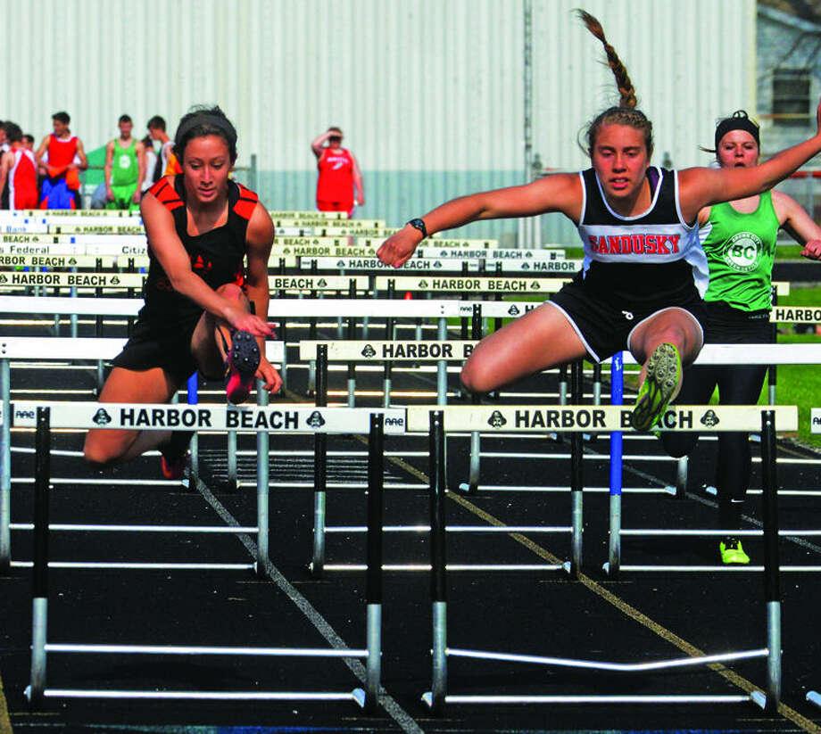 Ubly's Stephanie Young (left) and Sandusky's Katrina Tovar (right) cross the final set of hurdles in the 100 race, Monday during the Greater Thumb East League Meet hosted by Harbor Beach.