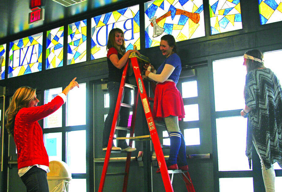 Art teacher Michelle McIntyre (far left) talks with senior students (from left) Isabel Humphrey-Phillips, Abby Lorencz and Amanda Talaski about their recent art project — roughly 70 hours using stained glass paint at the front entrance of Bad Axe High School.