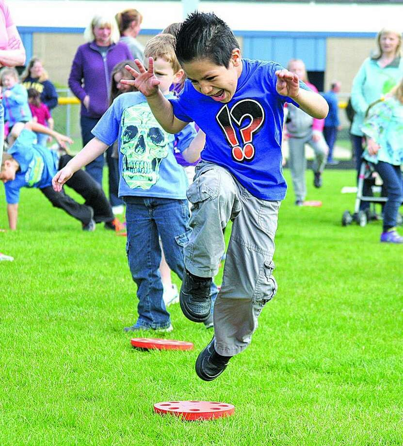 Kindergartener Aaron Cornejo leaps over a disc during the annual ACES Day event at the Bad Axe track complex. Bad Axe Elementary students joined more than 400,000 other students across the state in simultaneous exercise Wednesday morning. ACES stands for All Children Exercising Simultaneously. Photo:  Seth Stapleton/Huron Daily Tribune