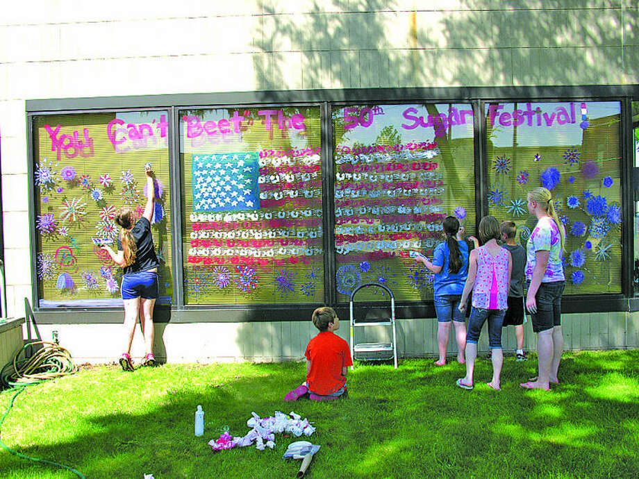 """Some of the more than two dozen children take part in the """"Kids Paint the Town"""" activity for the Michigan Sugar Festival last weekend in Muellerwise Park in Sebewaing. Business windows were painted in a patriotic theme for this week's 50th anniversary festival. Photo: Submitted Photo"""