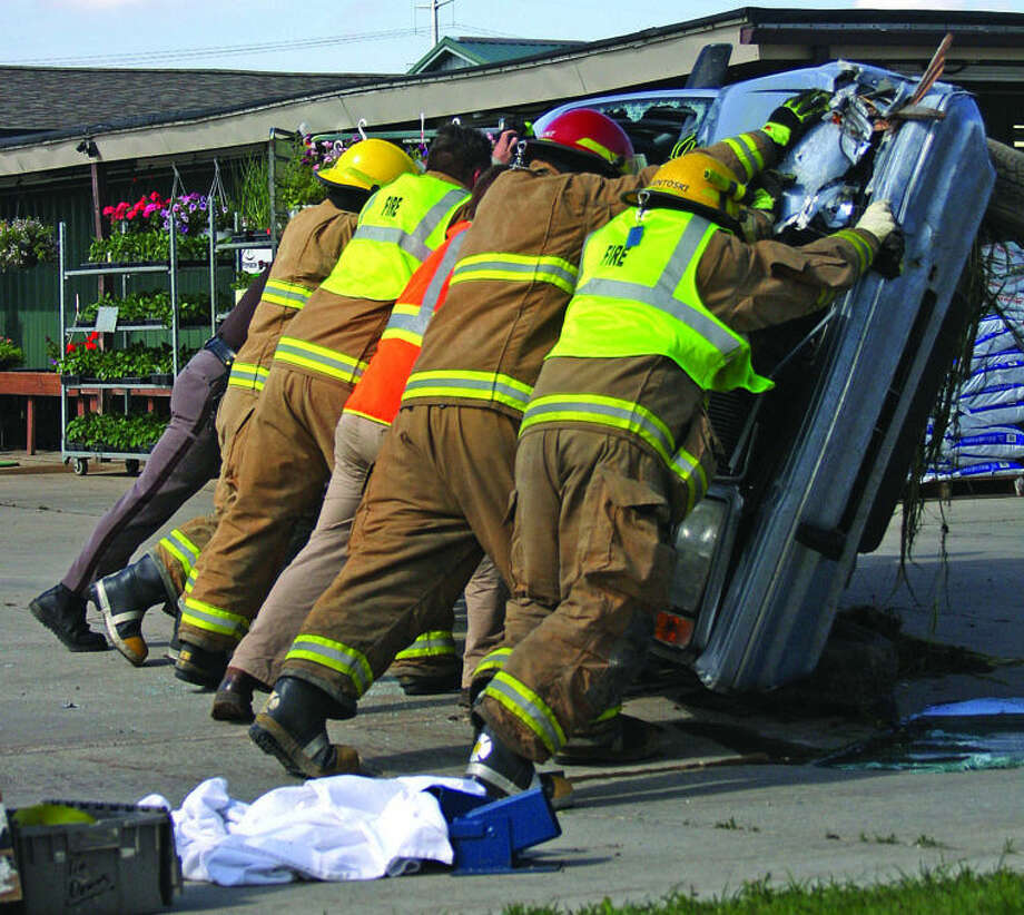Rescue workers turn a vehicle over after it crashed and flipped at Huron's Finest on North Van Dyke Road, north of Bad Axe, on Tuesday. Photo: Chris Aldridge/Huron Daily Tribune