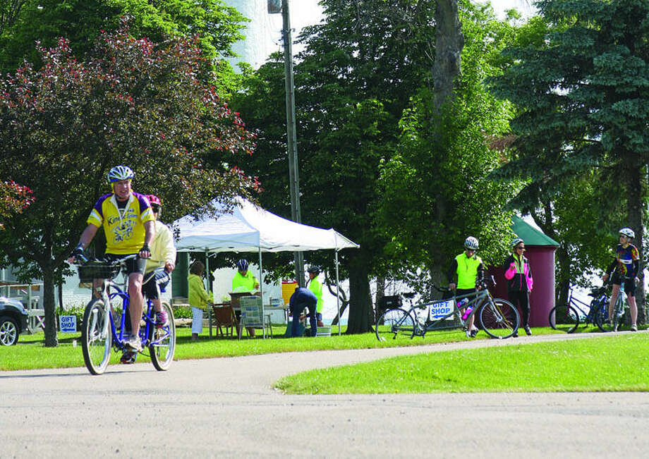 The first group of bike riders in the Tour di Lago arrive Saturday at Pointe aux Barques Lighthouse in Huron Township. They started their bike trek in Port Austin. Photo: Chris Aldridge/Huron Daily Tribune