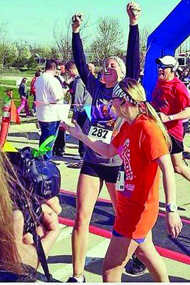 Bethany Grates of Caseville raises her arms in triumph after completing a 5K run in May. Photo: Submitted Photo