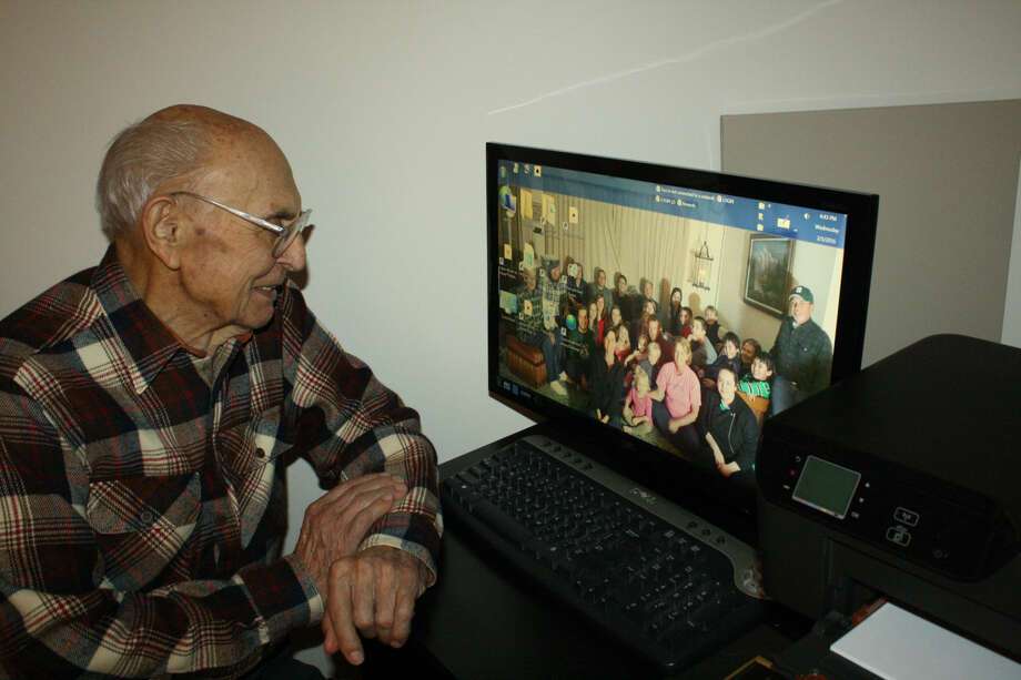 Virgil Bouck may be 95 years old, but he is still computer savvy. He keeps a portrait of his extended family as a wallpaper. Photo: Rich Harp/For The Tribune