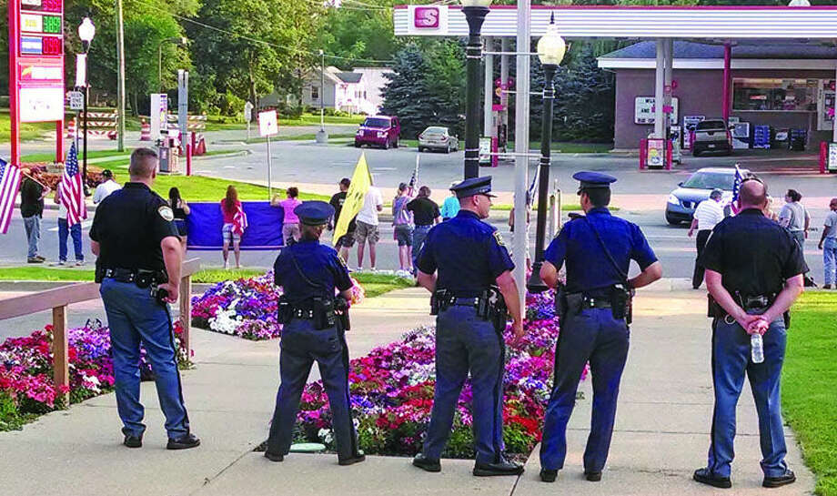 Vassar city police officers and Michigan State Police stand outside the Vassar Planning Commission meeting at Vassar City Hall on Monday night. Protesters opposed to the housing of Central American immigrants at Vassar's Wolverine Human Services facility are in the background. Photo: Tom Gilchrist/For The Tribune