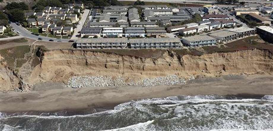 In this image provided by the California Coastal Records Project, cliff erosion is seen below the Esplanade Apartments in Pacifica, Calif., in 2009. Some came home from work to find the yellow tag on their front doors. Some were inside when the building inspectors unexcpectedly slapped the tags on their doors that required them to leave quickly. Living with the Pacific Ocean as your backyard has its benefits. But the crumbling ocean cliffs have forced dozens to move quickly and at a high cost. Stll, others remain, unsure of when the call to leave might come. (AP Photo/Kenneth Adelman/California Coastal Records Project via AP)