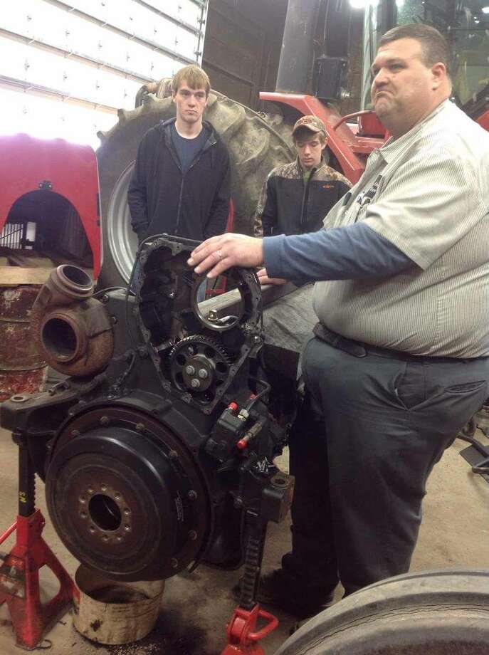 Right, Al Kuhn explains some of the enginerepairs completed at the Osentoski Equipment facility. (Submitted Photo)