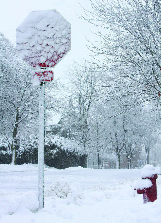Snow collects on a stop sign and fire hydrant this week in Bad Axe. Photo: Chris Aldridge/Huron Daily Tribune
