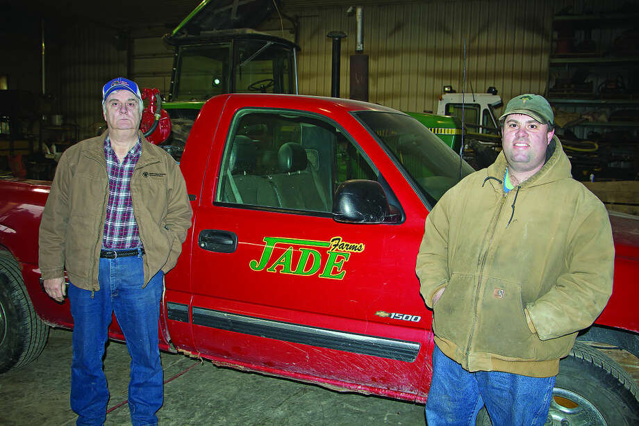 Doug and Greg Yackle stand beside a farm truck in the workshop of JADE Farms.