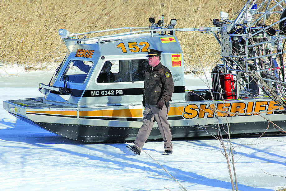 Huron County Sheriff Kelly J. Hanson walks besides his department's new rescue airboat at its unveiling Thursday near Bay Port. The boat will be available to serve several counties.