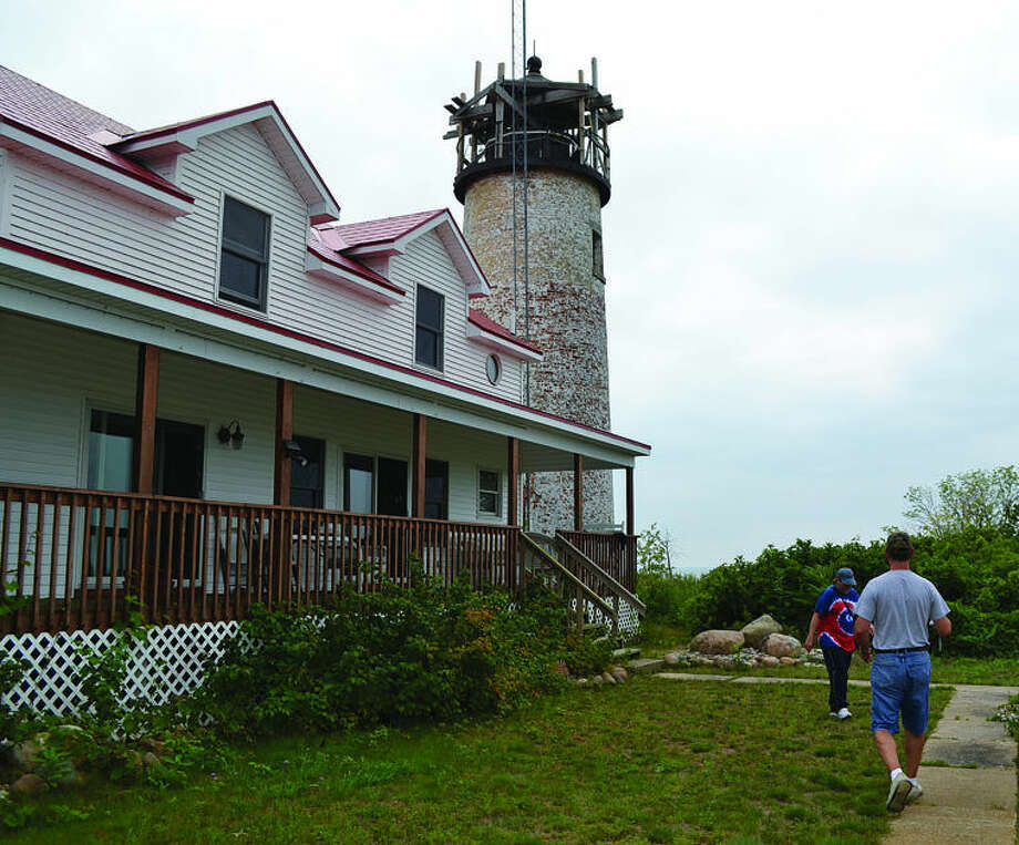 Charity Island visitors reach the lighthouse during last Sunday's excursion. The tower has helped boaters in Saginaw Bay for generations. Photo: Casey Johnson/Huron Daily Tribune
