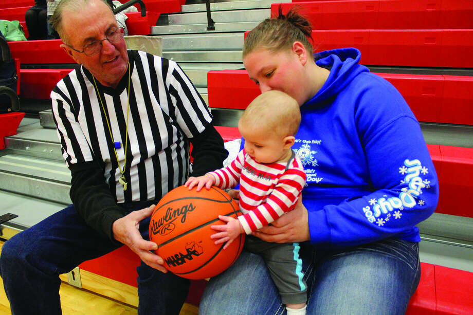 Wyatt Zinger, 6 months of Caseville, enjoys the Caseville Alumni game while a referee, Grandpa Barry Zinger, makes sure he gets in on the action. Also pictured is mother Whitney Zinger, a 2009 Caseville graduate. The alumni game took place during the weekend, and even year graduates suited up in white while the odd played in red. The White Team managed to win, 39-38. Photo: Amanda Triplett/For The Tribune
