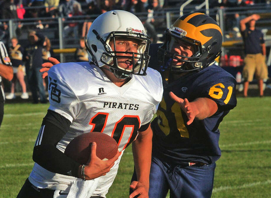 Harbor Beach quarterback Josh Schelke (10) eludes Bad Axe defender Jon Messing (61) on his way to an 11-yard touchdown run in the first quarter of the Pirates' 48-0 win, Thursday night in Bad Axe.