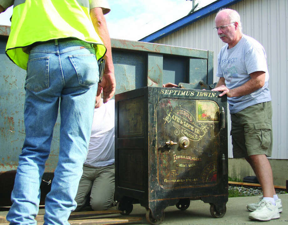 Ken Murray, right, helps move an antique safe from the former Murray's furniture store in Bad Axe. The safe dates from the 1800s and has the name of Bad Axe founder Septimus Irwin written on it. Photo: Chris Aldridge/Huron Daily Tribune