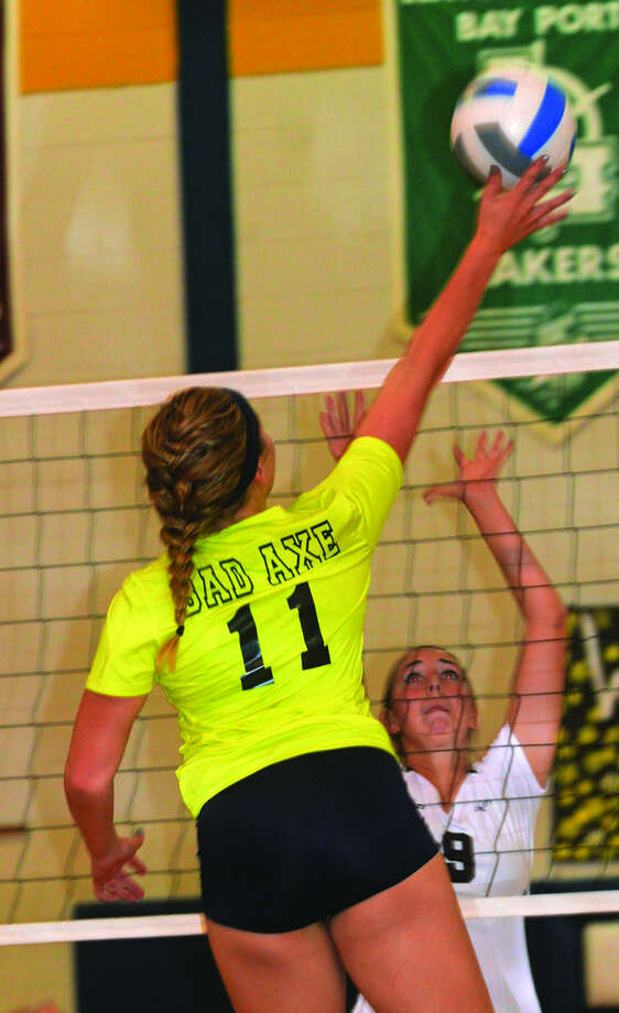 Bad Axe's Baylee Perez (11) goes for a kill against Cass City's Maegan LeValley (9) during Game 1, Tuesday in Bad Axe.