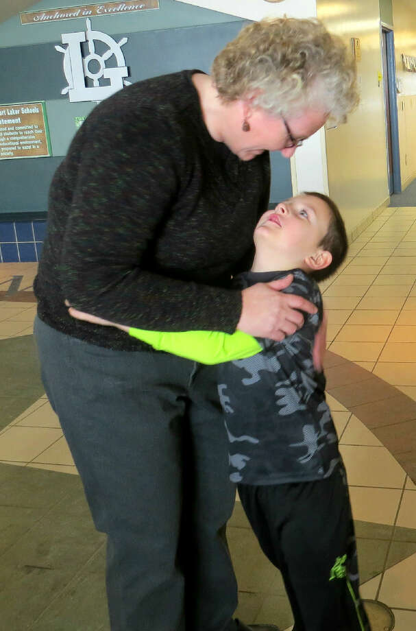 Laker Elementary Principal Kathy Dickens hugs a kindergarten student during the eight-hour hug event, during which she collected 621 hugs.