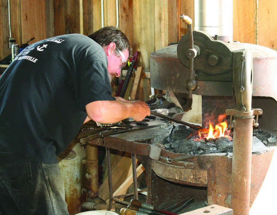 Shawn Baker shows his blacksmith skills while using an antique forge at an Octagon Barn exhibit.  Photo: Rich Harp/For The Tribune