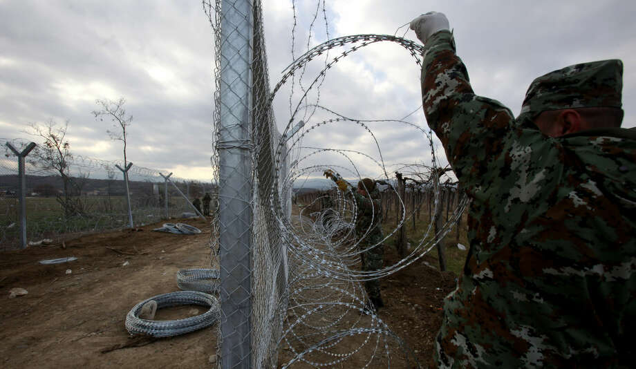 "FILE - In this February 8, 2016 file photo, Macedonian Army soldiers attach a razor wire to a fence on the border line with Greece, near the southern Macedonian town of Gevgelija, Six nations from Central and Eastern Europe meet Monday in Prague to discuss plans for a new ""line of defense"" for Europe that involves a double fence along Greece's northern border. (AP Photo/Boris Grdanoski, File) Photo: Boris Grdanoski"