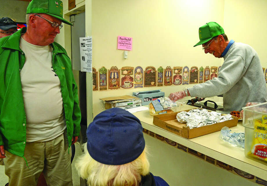 Henry Pionttowski, right, fills an order for a dozen barbecue sandwiches at the benefit for Thumb Veterans Organization Post No. 1 on Thursday at McDonald's Food & Family in Bad Axe. Photo: Chris Aldridge/Huron Daily Tribune