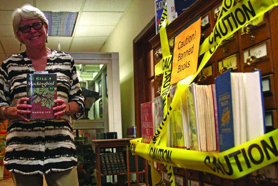 "Bad Axe Library Director Mimi Herrington holds ""To Kill a Mockingbird"" one of her favorite banned books. Photo: Chris Aldridge/Huron Daily Tribune"