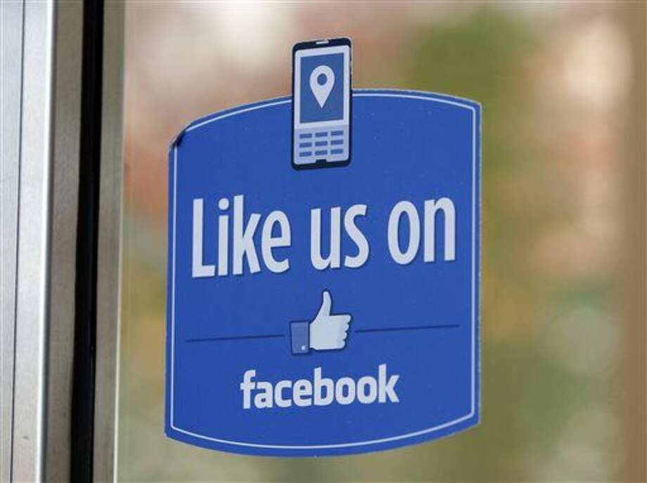 """In this Dec. 13, 2011 file photo, a sign with Facebook's """"Like"""" logo is posted at Facebook headquarters near the office for the company's User Operations Safety Team in Menlo Park, Calif. (AP Photo/Paul Sakuma)"""