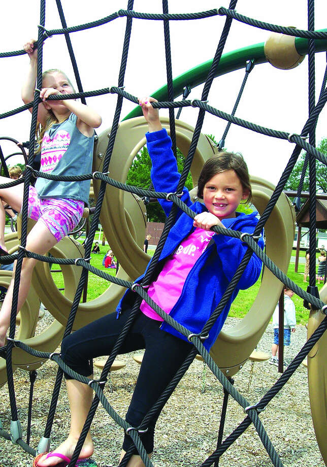 Amelia Capling,right, from Our Lady of Lake Huron Day Care, hangs on part of the playscape Thursday at Lincoln Park in Harbor Beach.  Photo: Rich Harp/For The Tribune