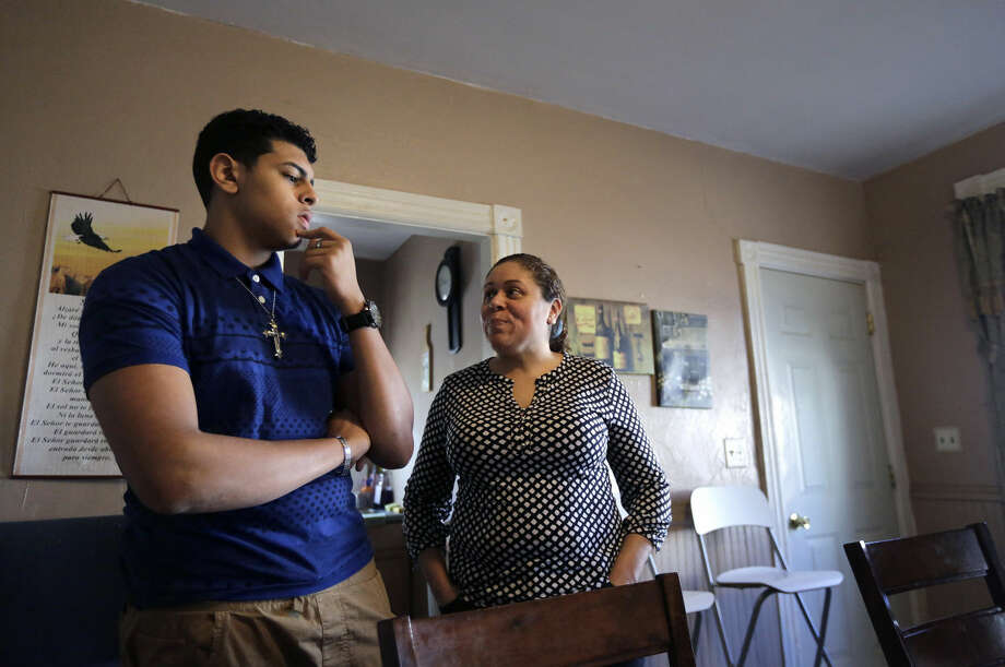 In this Wednesday, Feb. 17, 2016 photo Jay Henriquez, 16, left, and his mother Lisa Solano-Sanchez, right, both of Providence, R.I., talk in the kitchen of their home, in Providence. Solano-Sanchez believes her son, who was born in July of 1999, was poisoned in 2000 by consuming paint chips containing lead from a window sill in the home of his grandmother. (AP Photo/Steven Senne) Photo: Steven Senne