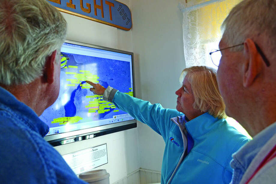Inside the museum at Lighthouse County Park, Bill Bonner, president of the Pointe aux Barques Lighthouse Society, left, and Roger Affholter, vice president, show Congresswoman Candice Miller a digital map of active ships Tuesday on the Great Lakes. Photo: Chris Aldridge/Huron Daily Tribune