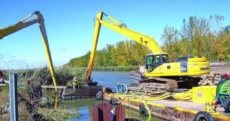 Workers from Mount Clemens-based Dean Marine & Excavating dredge the Sebewaing River late last week.