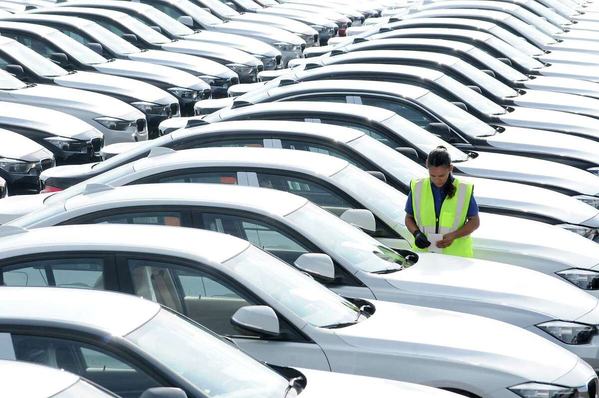 A driver stands in a lot of new vehicles that were recently unloaded at the new BMW Vehicle Distribution Center on Harborside Drive in Galveston Wednesday April 20, 2016. Houston auto sales haven't been as active as they were in the opening months of 2015, but the region is about to enter the typically higher-selling months of May through August. (Dave Rossman Photo)