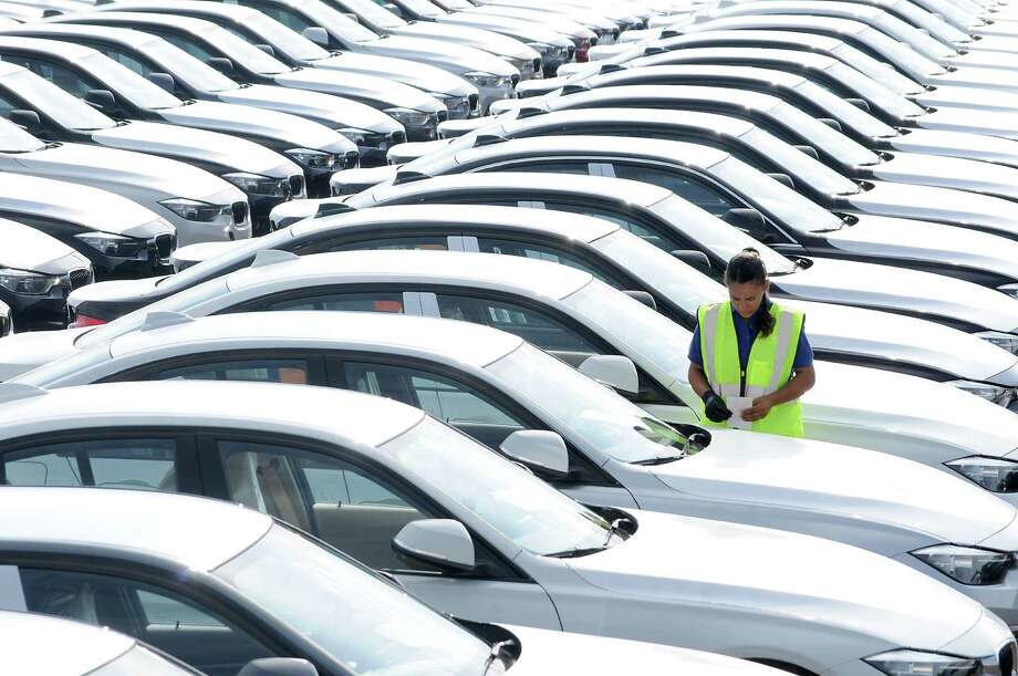 A driver stands in a lot of new vehicles that were recently  unloaded at the new BMW Vehicle Distribution Center on Harborside Drive in Galveston Wednesday April 20, 2016. Houston auto sales haven't been as active as they were in the opening months of 2015, but the region is about to enter the typically higher-selling months of May through August. (Dave Rossman Photo) Photo: Dave Rossman, Freelance / Dave Rossman