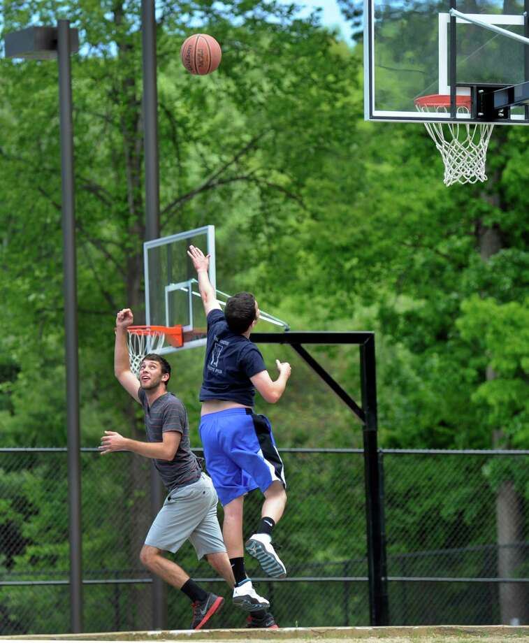 Joe Gilbert, 23, left and Dan McCarthy, 22, both of Brookfield, Conn., play on the basketball courts of the newly renovated Cadigan Park in Brookfield Thursday, May 21, 2015. Photo: Carol Kaliff / Carol Kaliff / The News-Times