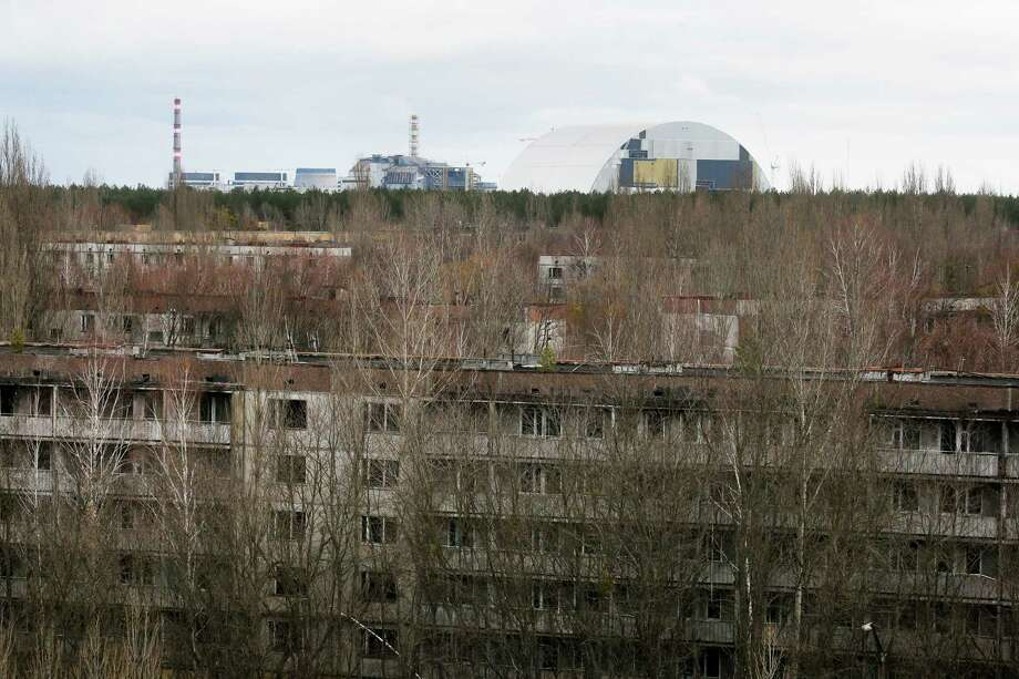 This photo taken Wednesday, March 23, 2016 shows abandoned apartment buildings  in the town of Pripyat near Chernobyl, Ukraine, with a chimney, left, at the destroyed reactor and a gigantic  arch-shape confinement to cover the remnants of the exploded reactor, in the back, at the Chernobyl nuclear power plant. Thirty years after the world's worst nuclear accident, the Chernobyl nuclear power plant is surrounded by both a hushed desolation and clangorous activity, the sense of a ruined past and a difficult future. (AP Photo/Efrem Lukatsky) Photo: Efrem Lukatsky / Associated Press / AP