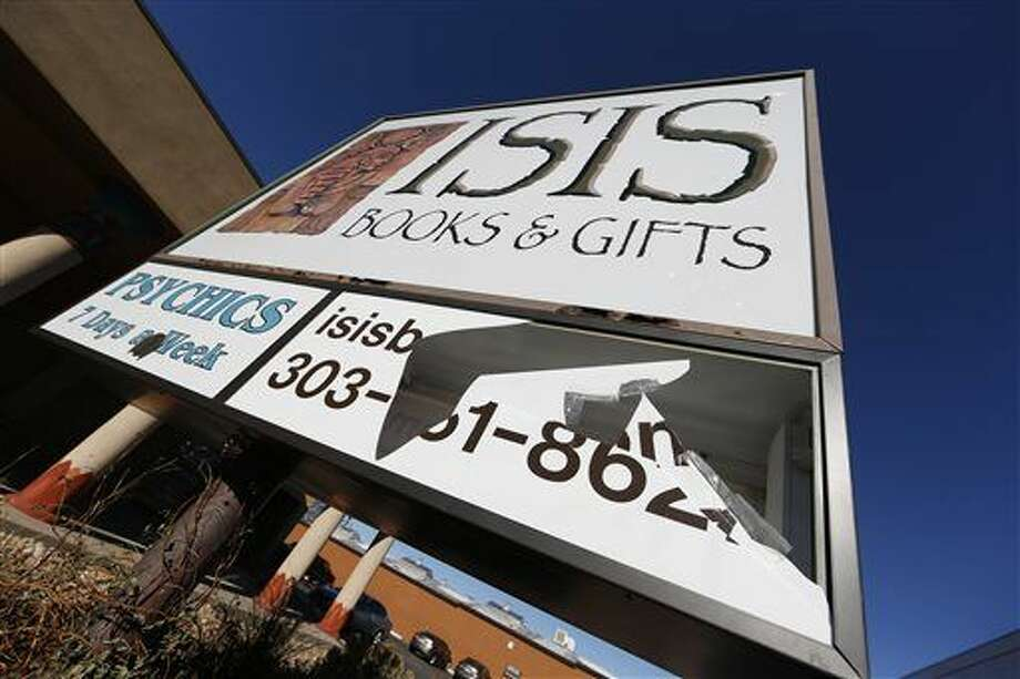 A panel of the sign outside Isis Books and Gifts store is broken Wednesday, Nov. 18, 2015, in Englewood, Colorado. Harrison and his wife, Karen, say that the New Age bookstore has been targeted by vandals because of the shop's name. The owner says the store is named after the Egyptian goddess Isis, and says the most recent vandalism is likely in response to Friday's terror attacks in Paris. (AP Photo/David Zalubowski)