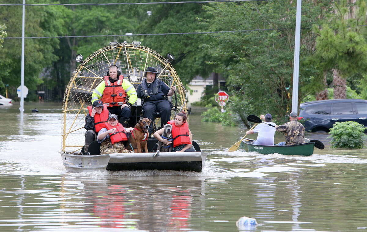 People and their pets are rescued from their homes near Nanes at Baltic in Houston, Texas, Wednesday, April 20, 2016.Thousands of people have been evacuated from their homes and major highways were closed after the rains that started Sunday overwhelmed Houston's bayous. Forecasters have issued another flash flood watch for Houston through Wednesday night. (Steve Gonzales/Houston Chronicle via AP) MANDATORY CREDIT