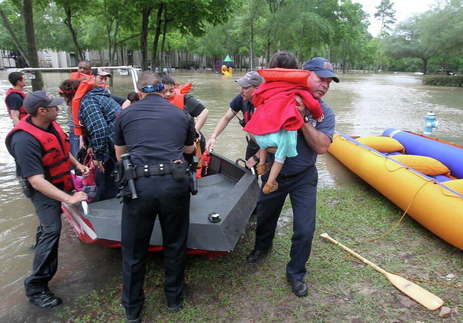 Spring firefighter Kenneth Eisfeldt lifts 3-year-old Valerie Negrete to safety as the family is evacuated from One Westfield Lake Apartment in Houston, Texas, Wednesday, April 20, 2016. The Negrete family had not been out of their home since Sunday. Thousands of people have been evacuated from their homes and major highways were closed after the rains that started Sunday overwhelmed Houston's bayous. Forecasters have issued another flash flood watch for Houston through Wednesday night. (Steve Gonzales/Houston Chronicle via AP) MANDATORY CREDIT Photo: Steve Gonzales, Associated Press / Houston Chronicle