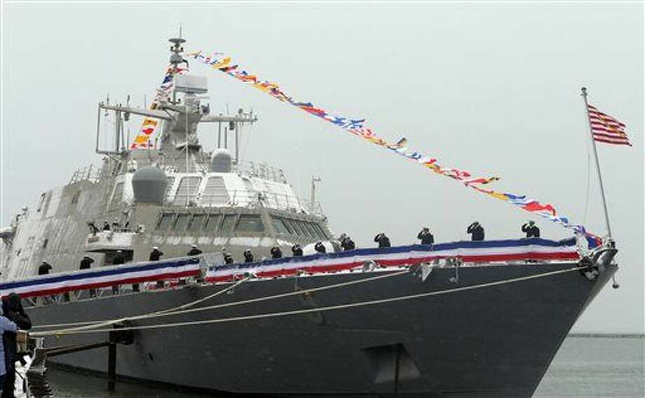 A crew salutes the raising of flag during a ceremony at Veterans Park in Milwaukee, Saturday, Nov. 21, 2015, to commission the new USS Milwaukee littoral combat ship. The warship, built in Wisconsin, is now ready to report for duty in the South China Sea. (Rick Wood/Milwaukee Journal-Sentinel via AP) Photo: Rick Wood