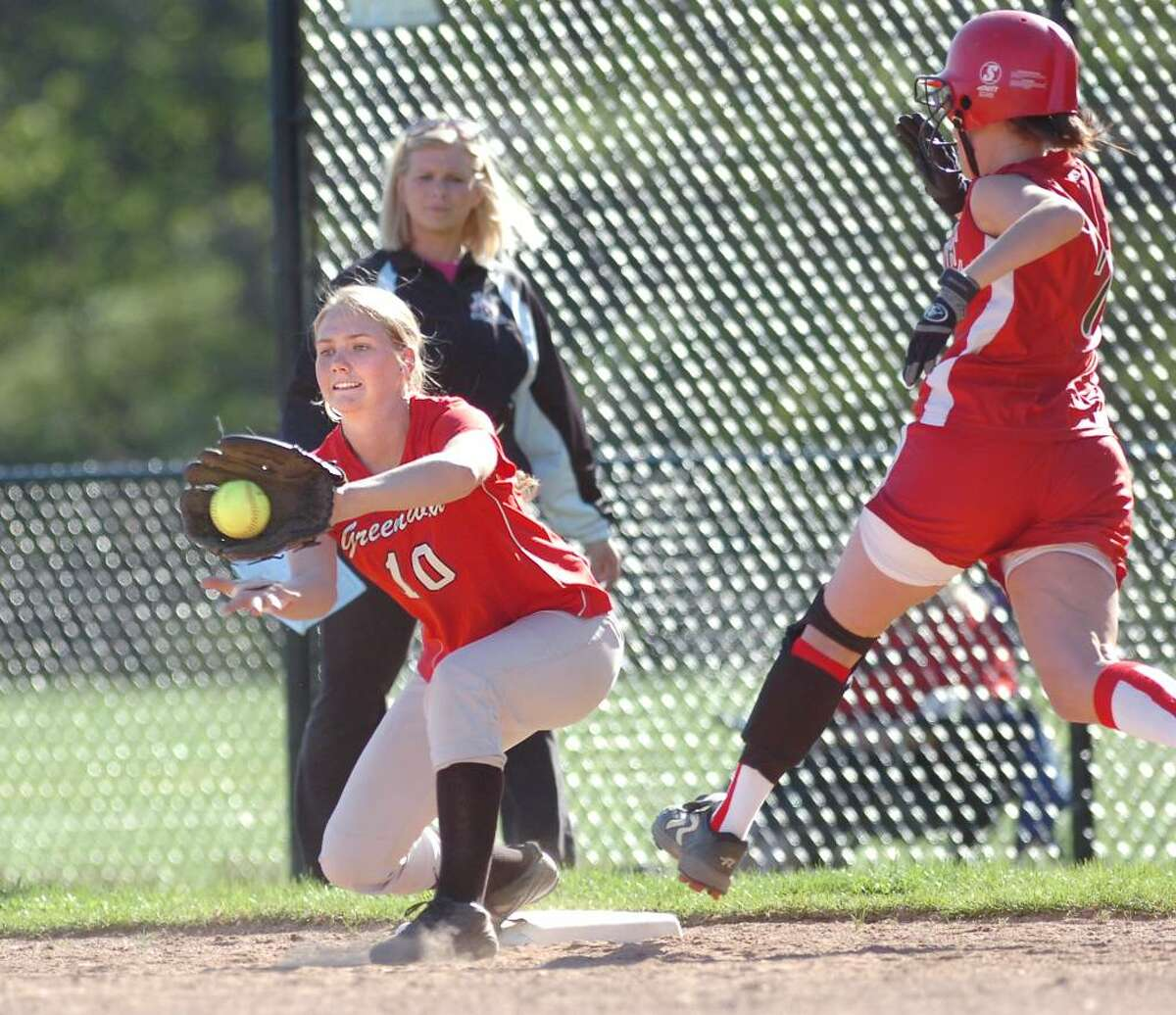Top of the 4th inning, Bianca Passaniti of Fairfield Warde High School, # 7, right, is out by a hair as Greenwich High School first basewoman, Sarah Jarombeck, # 10, left, takes the throw that just beats the Passaniti, at GHS, April 14, 2010.