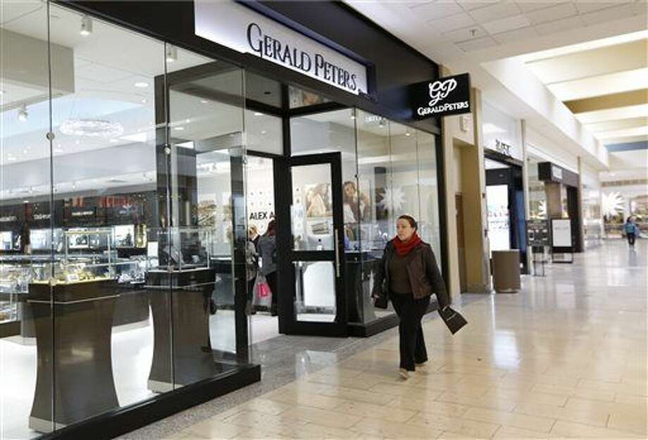 In this Wednesday, Nov. 18, 2015, photo, a shopper walks past Gerald Peter jewelers at the Staten Island Mall, in New York. The store, one of three in the mall owned by Jerry Amerosi, will open at 6 p.m. on Thanksgiving and stay open until midnight. Amerosi's lease at the mall, which has big stores, including Macy's, J.C. Penney and Sears, requires him to open. That's the norm for most malls, whose landlords will fine retailers, in some cases over $1,000, if they stay closed. (AP Photo/Kathy Willens)