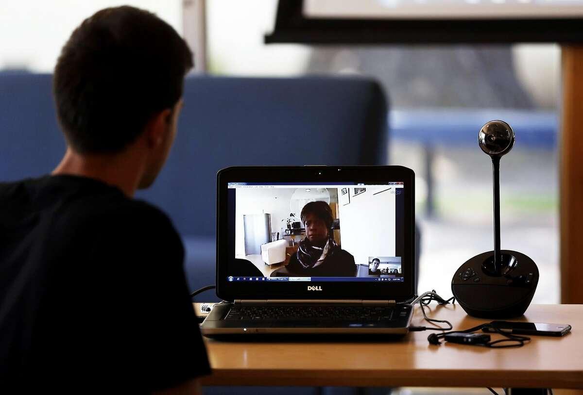 Junior Ashot Arutyunyan (left) speaks with robot Bina48 over video conference at Notre Dame de Namur University in Belmont, California, on Wednesday, April 20, 2016.