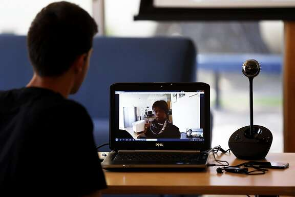 Junior Ashot Arutyunyan (left) speaks with robot Bina48 over video conference at Notre Dame de Namur University in Belmont, California, on Wednesday, April 20, 2016.
