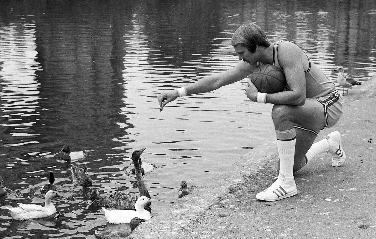 Warriors star Rick Barry feeds the ducks during team picture day in 1973.