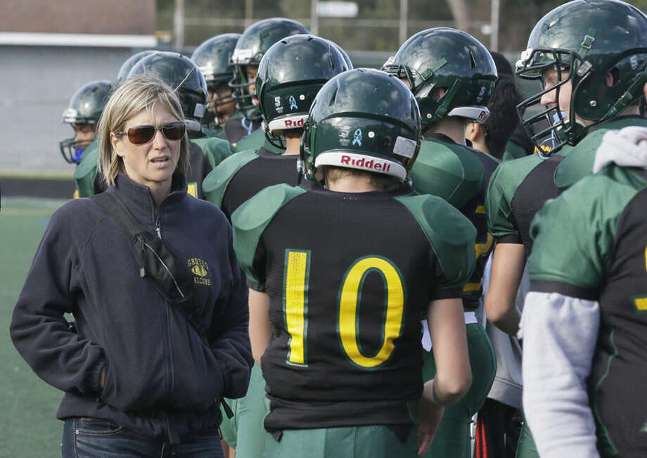 In this Oct. 1, 2015, photo, Birmingham Groves athletic trainer Kelly Salter walks on the sidelines during a freshman football game in Beverly Hills, Mich. Salter attends all of the high school sporting events and administers assessment tests to athletes who suffer concussions. Groves is one of 62 Michigan high schools participating in a unique pilot concussion program that does baseline testing of athletes in football and other sports. (AP Photo/Carlos Osorio) Photo: Carlos Osorio