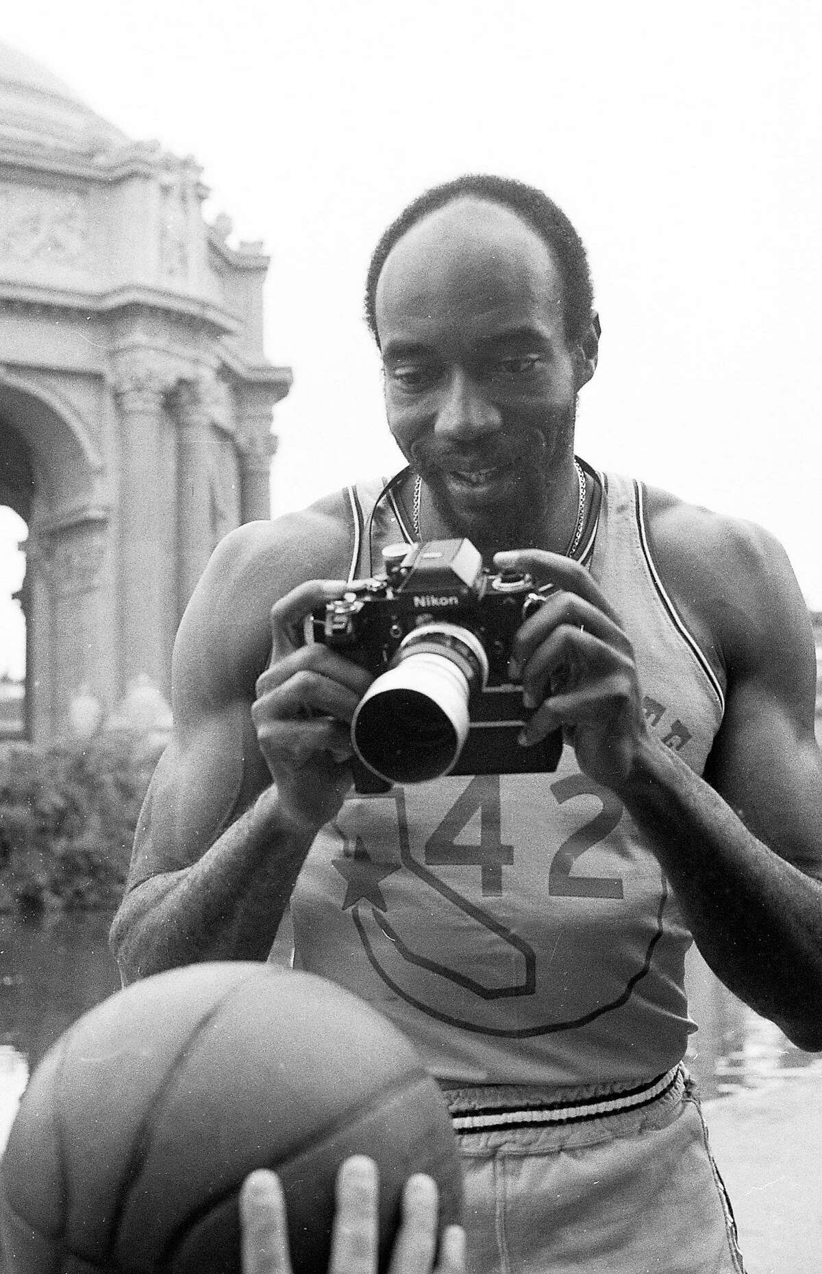 Nate Thurmond poses with a camera on Sept. 11, 1973,in front of the Palace of Fine Arts on Warriors picture day.