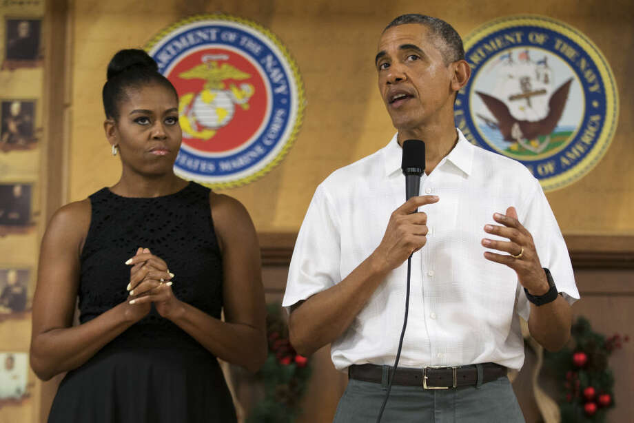 First lady Michelle Obama looks on as President Barack Obama speaks during an event to thank service members and their families at Marine Corp Base Hawaii, on Friday, Dec. 25, 2015, in Kaneohe Bay, Hawaii. (AP Photo/Evan Vucci) Photo: Evan Vucci
