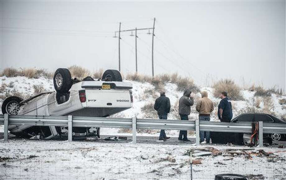 People stand by after a rollover accident along Interstate 25 northbound just south of Albuquerque, N.M., Saturday, Dec. 26, 2015. A flurry of snow began to blanket Albuquerque, Santa Fe and other cities Saturday afternoon amid warnings of a record-setting blizzard being on the horizon. (Roberto E. Rosales/The Albuquerque Journal via AP)
