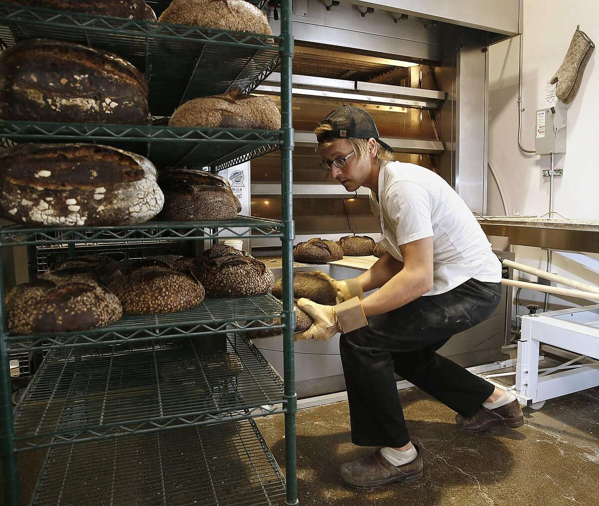 Pain baker Chase Agee removes baked bread from the oven to cool on racks in San Mateo, California on tuesday, april 19, 2016.
